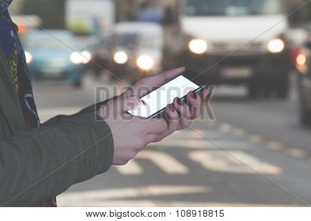 Using cellphone outdoors - with defocused city traffic.
