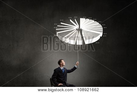 Businessman in chair holding diagram pie on rope