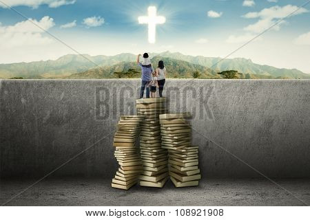 Family Using Book To See A Cross