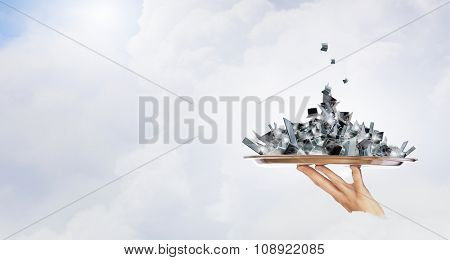 Hand holding metal tray with pile of electronic devices