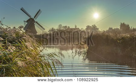 Dutch Windmill In Hazy Wetland