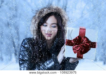Girl In Warm Clothes Holds A Gift