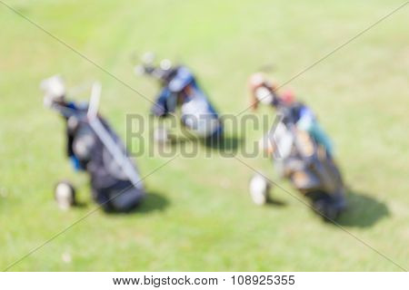 Blurred Photo Of Golf Bags Leaving On Green Field During The Golf Match.