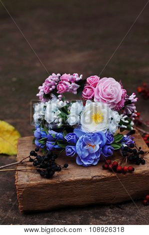 Hoop from flowers, wreath with colored flowers. Handmade flowers wreath on outdoor wooden stand. Acc