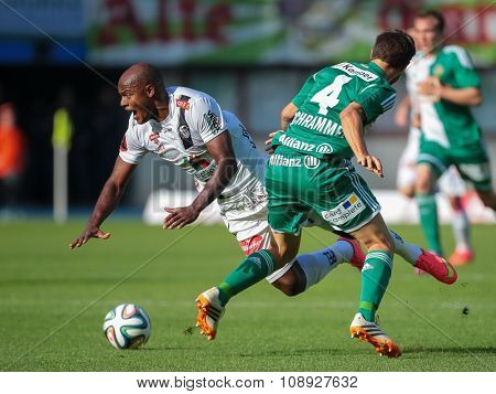 VIENNA, AUSTRIA - SEPTEMBER 20, 2014: Silvio de Oliveira (#8 Wolfsberg) and Thomas Schrammel (#4 Rapid) fight for the ball in an Austrian soccer league game.