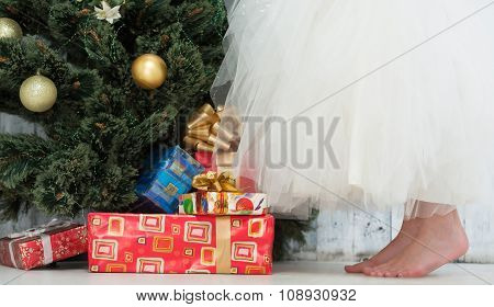 Girl in white dress decorating New Year tree