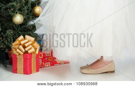 Girl in white dress decorating New Year tree at home