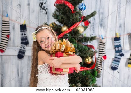 Teenage girl holding Christmas present in front of New Year tree