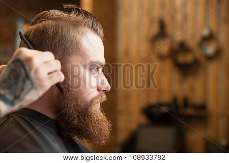 Professional young barber with a comb at beauty shop
