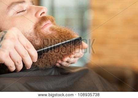 Skillful male hairstylist is working with comb