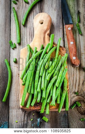 Pods Of Fresh Organic Green Beans In A Wooden Board