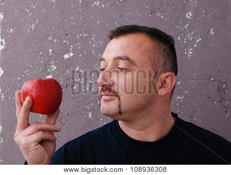 Man looking on an apple