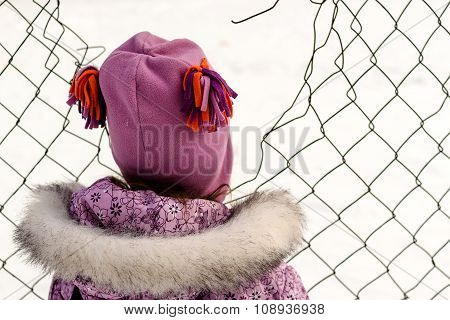 Young Girl Looking Through Broken Chain Link Fence