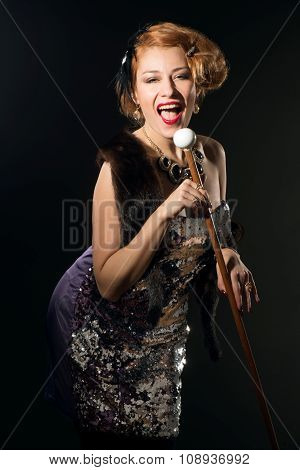 woman in vintage style dress singing and holding microphone