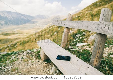 Phablet Smartphone On Wood Bench In Mountains