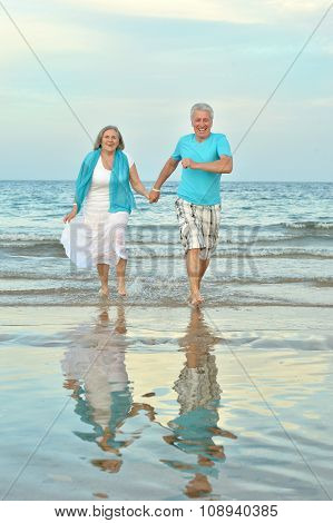 Elderly couple walking along  seashore