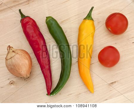 Bright Chili Peppers, Cherry Tomatoes And Onion On Wooden Board