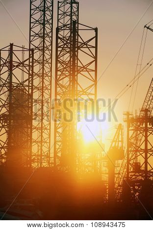 Industrial Background: Closeup Of Shipyard Construction Site With Silhouettes Of Cranes And Steel St