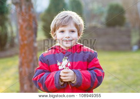 little kid boy in red jacket holding snowdrop flowers