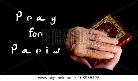 Pray For Paris. The Hands Of Senior Woman On The Koran