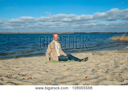 Joyful  Man, Wearing Casually,sitting On The Coast, Relaxing And Enjoying Life In Magic Autumn Day.
