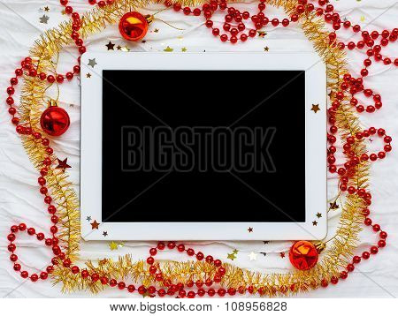 Tablet On Winter Holiday Background. Christmas Decorations - Red And Yellow Tinsel, Star Sparkles