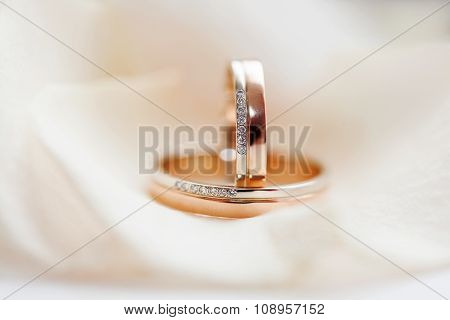 Golden Wedding Rings With Diamonds Lie On Silk Fabric. Symbol Of Love And Marriage.