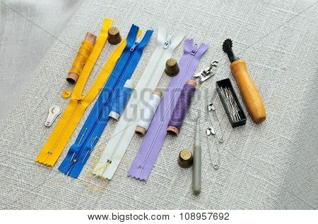 Items for sewing. Spools of sewing thread, pins, needles, buttons, thimbles, castle of zipper.