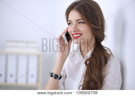 Smiling businesswoman talking on phone sitting at the office