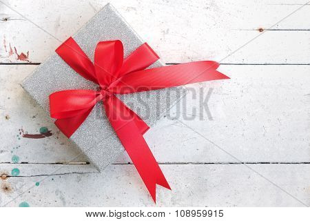Silver Gift Box With Red Ribbon Bow On Vintage Background