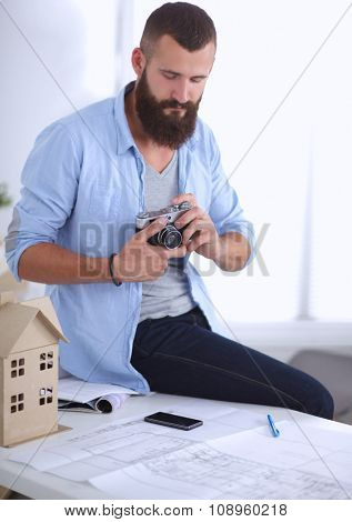 Portrait of male designer sitting on a table with blueprints an