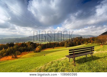 Panoramic sunny autumn alpine view with bench