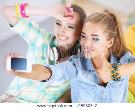 Two girls taking pictures on the phone at home and showing ok
