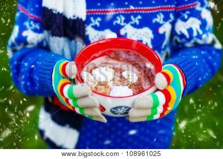 Hands of child holding big cup of chocolate drink in winter