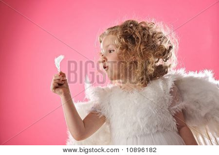 Beautiful small angel girl holding a feather