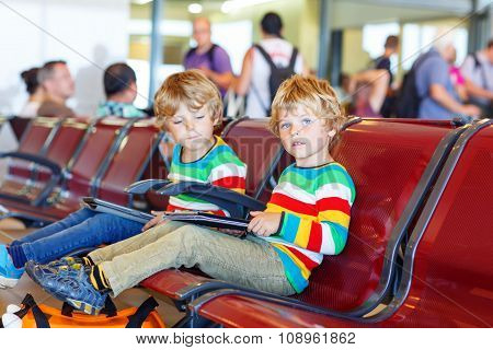 Two tired little sibling boys at the airport