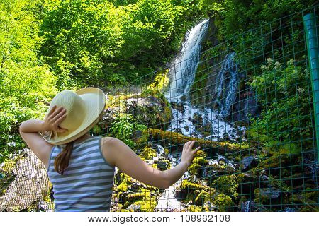 Young tourist looking at waterfall