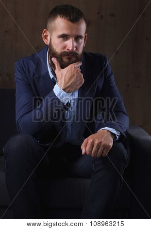 Businessman sitting the sofa in office lobby, isolated on dark