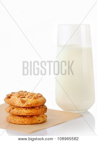 Stack of three homemade peanut butter cookies on baking paper and glass of milk