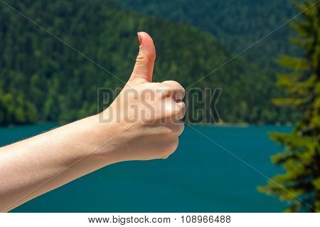 Thumb on the background of a lake