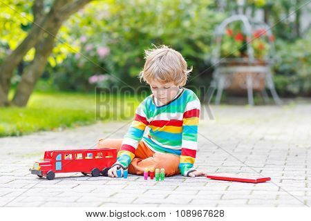 Active kid boy playing with red school bus and toys