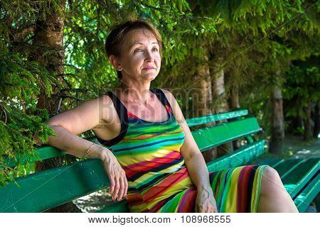 Old woman sitting under the tree