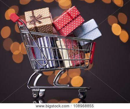 Shooping cart full of gift boxes on dark background