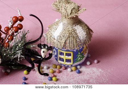 Christmas Hut, Monkey, Branch Spruce With Red Berries On A Pink Background.