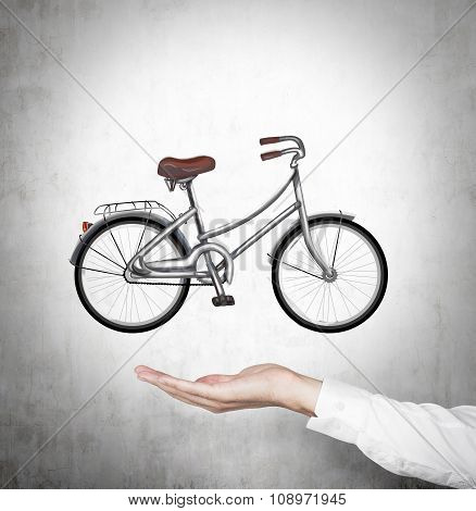 A Hand In Formal Shirt Holds A Bicycle Which Is Drawn On The Concrete Wall.