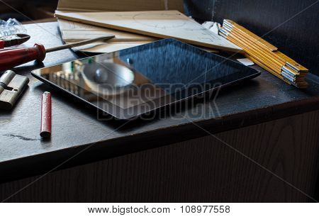 Tablet On A Dark Cupboard Surrounded By Tools In A Dirty Basement