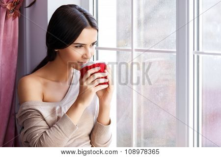 Young woman sitting near window