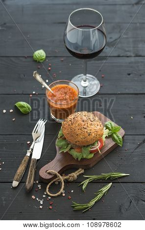 Fresh homemade burger on dark serving board with spicy tomato sauce, sea salt, herbs and glass of re