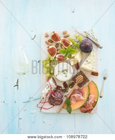 Wine and snack set. Figs, grapes, nuts, cheese variety, meat appetizers, herbs, glass on light blue