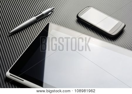 Blank Business Smartphone And A Pen Lying Next To A Tablet With Reflection Above A Carbon Background